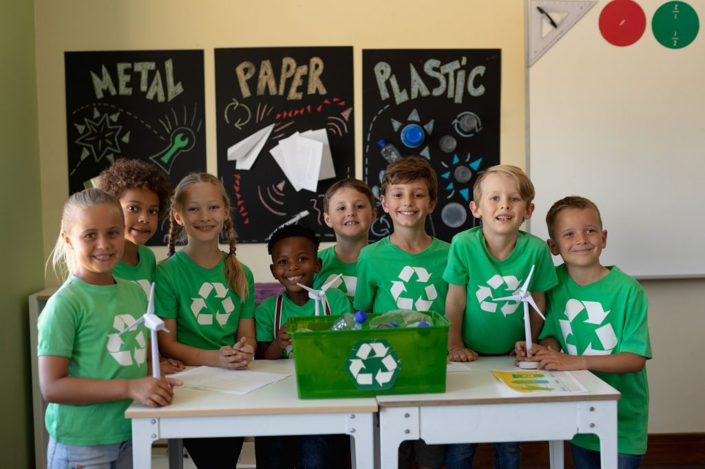 Group of schoolchildren wearing green t shirts with a white recycling logo on them