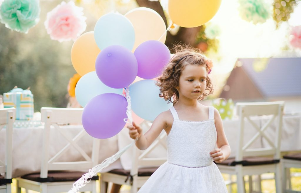 Portrait of small girl playing with balloons outdoors on garden party in summer