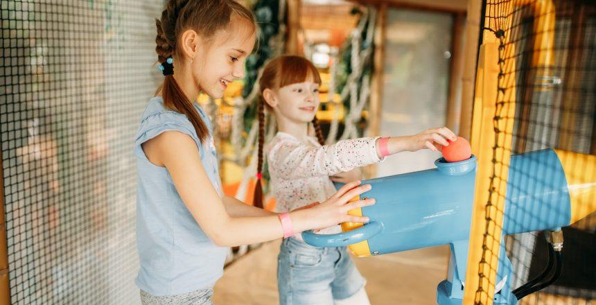 Two little girls plays air gun in game center